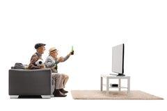 Due uomini maturi hanno messo su calcio di sorveglianza del sofà sulla televisione Immagine Stock Libera da Diritti