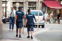 Due uomini municipali della polizia che camminano nella via che controlla le automobili parcheggiate Fotografie Stock Libere da Diritti