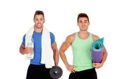 Due uomini muscolari con l'attrezzatura della palestra Fotografia Stock Libera da Diritti