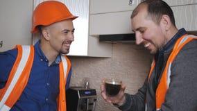 Due uomini nei vestiti da lavoro ed in caschi protettivi bevono il caffè preparato nella cucina durante una pausa stock footage
