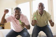 Due uomini nella sala con incoraggiare delle bottiglie da birra immagini stock libere da diritti