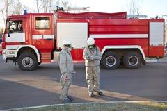Due uomini nella serie chimica di protezione sul fondo del camion dei vigili del fuoco fotografia stock libera da diritti