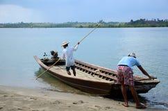 Due uomini ordinano il traghetto fuori attraverso il fiume Fotografia Stock