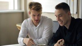 Due uomini parlano a vicenda durante la pausa caffè stock footage