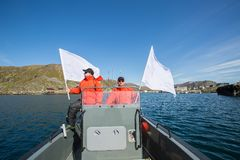 Due uomini in rivestimenti rossi con le bandiere Una barca Sea Fotografie Stock Libere da Diritti