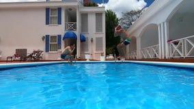 Due uomini saltano nella piscina stock footage