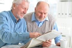 Due uomini senior che si siedono alla tavola ed alla lettura Immagine Stock Libera da Diritti