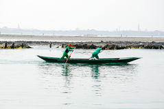 Due uomini si esercitano remando una barca a Venezia, Italia Immagini Stock