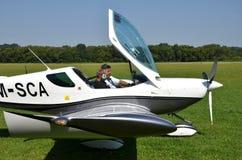 Due uomini si siedono dall'nell'aeroplano guidato da elica ultraleggero e si preparano per decollare Immagini Stock Libere da Diritti