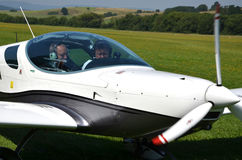 Due uomini si siedono dall'nell'aeroplano guidato da elica ultraleggero e si preparano per decollare Immagine Stock