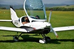Due uomini si siedono dall'nell'aeroplano guidato da elica ultraleggero e si preparano per decollare Fotografia Stock