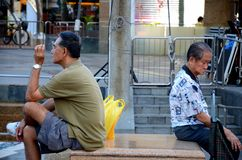 Due uomini si siedono di nuovo alla parte posteriore in una piazza pubblica nella proprietà di Singapore Toa Payoh HDB Fotografia Stock