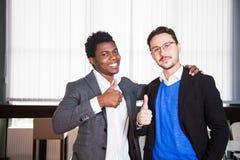 Due uomini sorridenti in vestiti esaminano la macchina fotografica, ritratto degli uomini d'affari Fotografie Stock Libere da Diritti