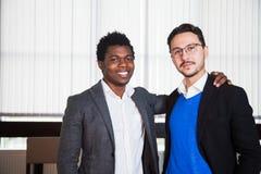 Due uomini sorridenti in vestiti esaminano la macchina fotografica, ritratto degli uomini d'affari Fotografia Stock
