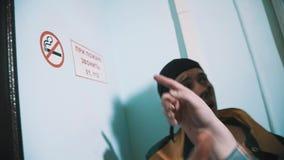 Due uomini sporchi che leggono i segni e che impediscono il fumo, la porta aperta e si allontanano video d archivio
