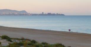 Due uomini stanno camminando seguendo la linea della spiaggia sabbiosa contro lo sfondo della città di mattina immagine stock libera da diritti