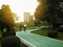 Due uomini stanno ciclando su una pista ciclabile in un parco pubblico immagini stock