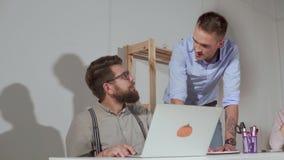 Due uomini stanno comunicando in ufficio nel giorno lavorativo, uno sta sedendosi al computer portatile stock footage