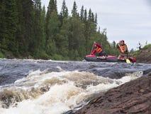 Due uomini su un catamarano che galleggia sul fiume Immagine Stock Libera da Diritti