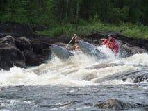 Due uomini su un catamarano gonfiabile sormontano la soglia sul fiume Immagini Stock Libere da Diritti