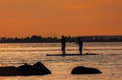 Due uomini sui loro bordi di pagaia nell'oceano Pacifico durante il tramonto arancio Fotografia Stock Libera da Diritti