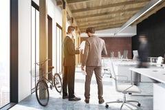 Due uomini in ufficio con un manifesto e una bici Fotografie Stock Libere da Diritti