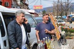 Due uomini vendono il brandy casalingo della cotogna sul mercato degli agricoltori di Pirot Fotografia Stock