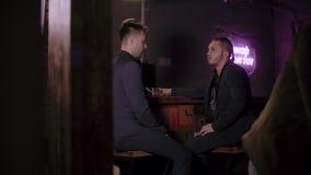 Due uomini in vestiti bevono il whiskey in una barra archivi video
