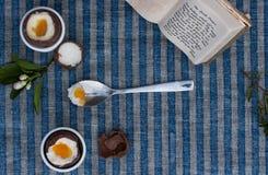 Due uova di Pasqua del cioccolato, cucchiaio con tuorlo e coperture accanto a Pra Immagini Stock Libere da Diritti