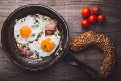 Due uova fritte con bacon e cipolla, pomodoro e pane dal lato Fotografia Stock