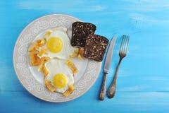 Due uova fritte con pepe e due fette di pane di segale su un plat Immagini Stock