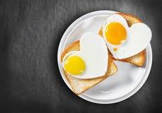 Due uova fritte in forma di cuore e pane tostato fritto Immagine Stock