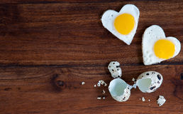 Due uova fritte in forma di cuore su fondo di legno Immagine Stock