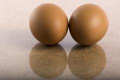 Due uova marroni del pollo hanno riflesso in una tavola di legno Immagini Stock