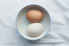 Due uova in tazza sul fondo del tessuto Fotografia Stock