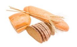 Due varie pagnotte di pane integrale, di pane nero e delle spighette Fotografia Stock