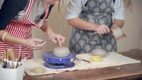 Due vasai femminili stanno elaborando le ciotole ceramiche nel negozio delle terraglie, primo piano video d archivio