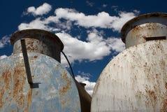 Due vecchi carri armati arrugginiti contro un cielo blu drammatico fotografia stock