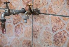 Due vecchi rubinetti di acqua ad una parete all'aperto delle mattonelle Fotografie Stock