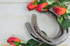Due vecchie scarpe del cavallo accoppiate con le rose rosse di seta su un fondo di legno rustico imbiancato fotografie stock libere da diritti