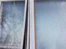 Due vecchie strutture della finestra di legno, dipinte nel bianco con vetro grigio fangoso, in vetro riflette il cielo e gli albe Fotografie Stock Libere da Diritti