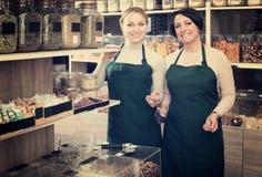 Due venditori femminili che indossano grembiule Immagine Stock