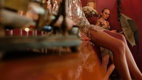 Due vestiti brillanti da modelsin professionale per un tiro di foto ragazza che si siede sulla tavola della barra stile d'annata, video d archivio