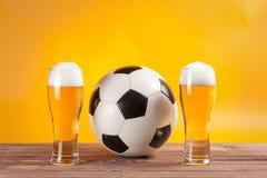 Due vetri con birra e pallone da calcio vicino alla ripresa esterna della TV Fotografia Stock