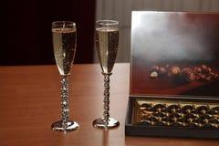 Due vetri con champagne e cioccolato sulla tavola Immagine Stock