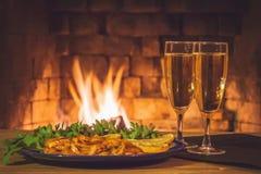 Due vetri con champagne e un piatto con i gamberetti, il limone ed i verdi su una tavola di legno contro lo sfondo della a fotografia stock