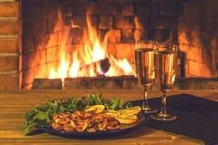 Due vetri con champagne e un piatto con i gamberetti, il limone ed i verdi su una tavola di legno contro lo sfondo della a immagine stock