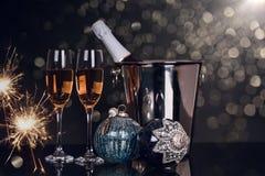 Due vetri con champagne, la bottiglia e gli ornamenti di Natale immagine stock libera da diritti