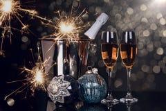 Due vetri con champagne, la bottiglia, le stelle filante e gli ornamenti di Natale immagine stock libera da diritti