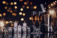 Due vetri con champagne, le stelle filante e la decorazione di Natale immagine stock